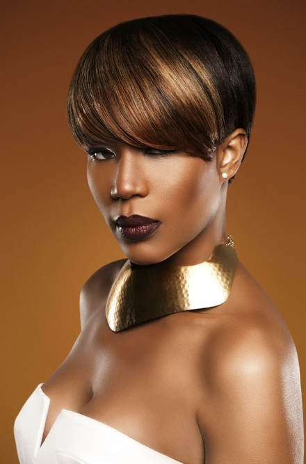 A black female model, modelling her hair. Her hair is cut into a short bob and the front has a big thick finge that has been highlighted brown.