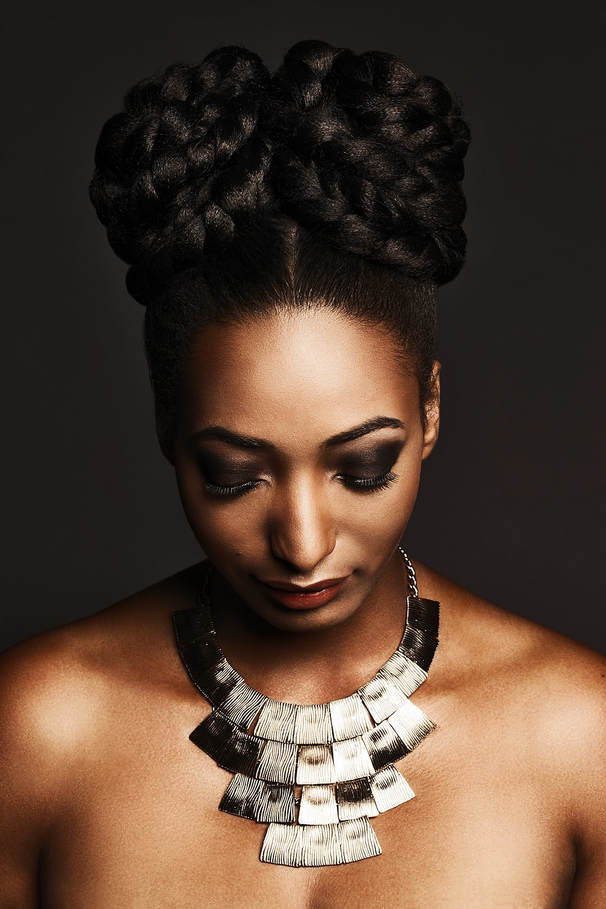 Black female model, modelling her hair. She is wearing her hair up ub elaborate plaited bunches. Her eyes are looking down.