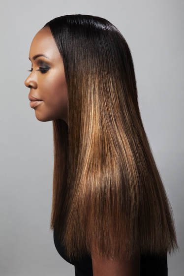 Black femal model, modelling her hair which is straight and pass her shoulders. Her hair has been highlighted different shades of brown and gold.