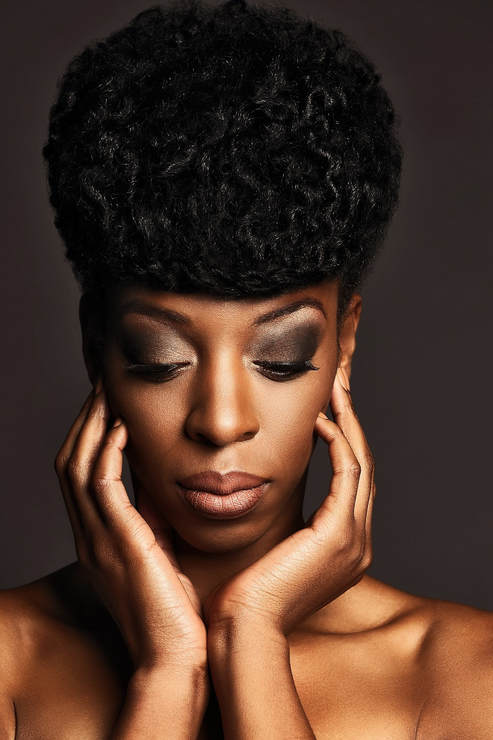 Black female model with a fancy updo. Her hands are y the side of her face and her eyes are looking down.