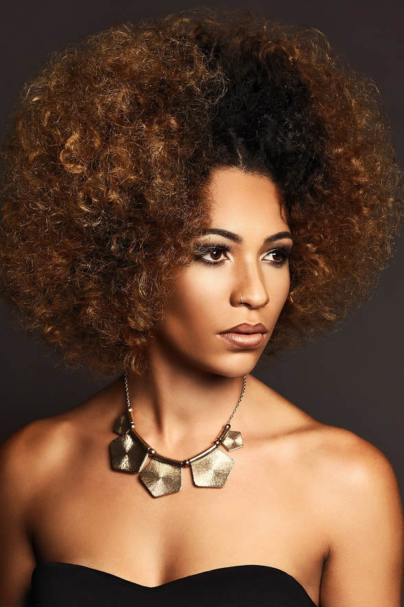 Black female model, modelling her hair. Her hair is soft, short and curly. The ends have been dyed brown and the middle is black.