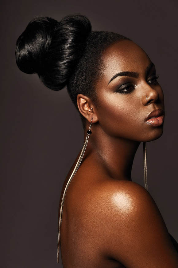 Black female model, modelling her hair. She is wearing a smooth looking updo and is wearing very long dangly earrings.
