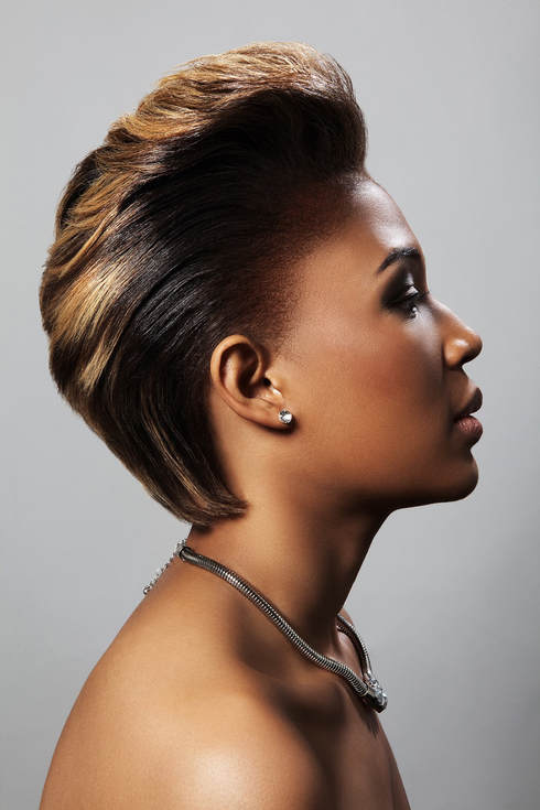 Black female, modelling her hair that has been cut short and is slicked back at the sides with a quif at the front. The hair has been been dyed a golden brown colour.