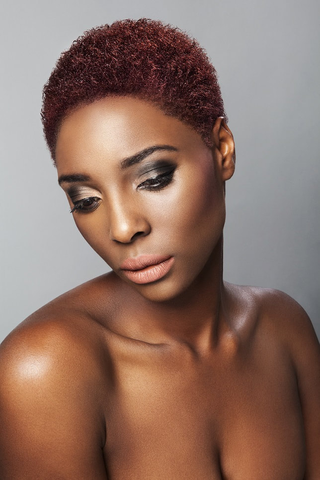 Black female model, modelling her hair that is short and has been coloured burgundy.