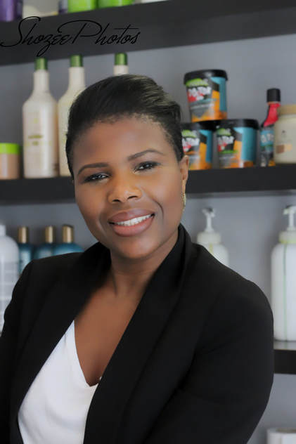 The owner of Marieme D Hair smiling and looking into the camera. She is wearing a white t-shirt and a smart black jacket.