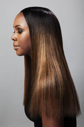 Black model, modelling hair that is long and straight and reaches past her shoulders. Her hair has also been coloured different browns.
