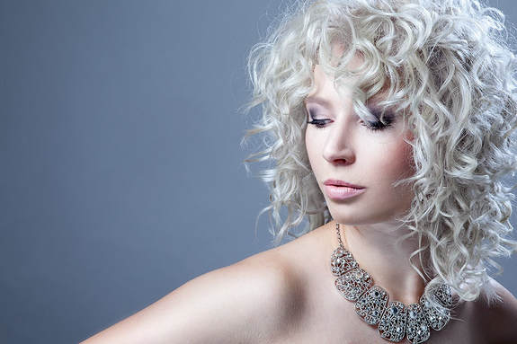 White model, modelling hair that  has been layered and is white and curly.