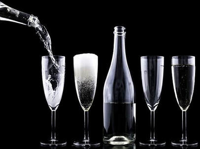 A short line up of flute glasses and bottle against a black background. To the left there is another bottle pouring fizzy drink into one of the flute glasses.
