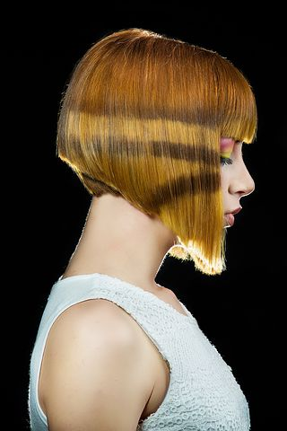 White model that is modelling hair. She is in side on profile and looking at the floor. Her hair is an angeled bob with fringe.