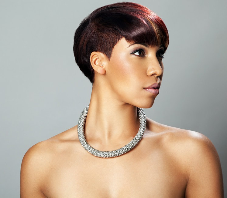 Black model, modelling hair that is cropped in a short bob with fringe. Her hair has been coloured burgundy.